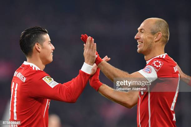 James Rodriguez and Arjen Robben of FC Bayern Muenchen celebrate their teams second goal during the Bundesliga match between FC Bayern Muenchen and...