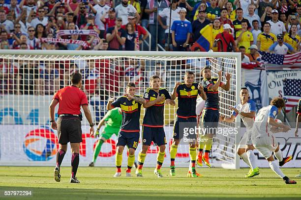 James Rodriguez Daniel Torres Edwin Cardona and Sebastian Perez of Colombia defend against a penalty in the first half during a group A match between...