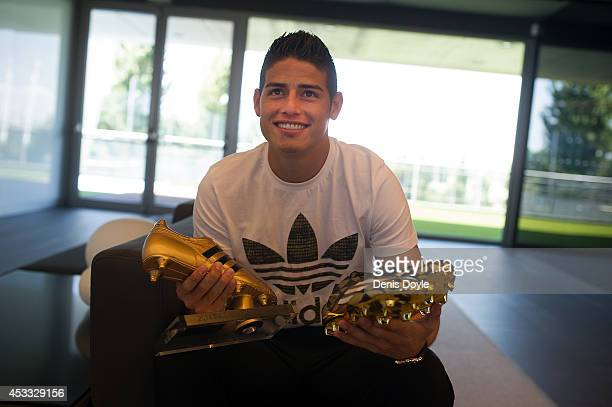 James Rodriguez holds his adidas adiZero boots he was presented with at Real Madrid's Valdebebas in recognition of scoring the most goals during the...
