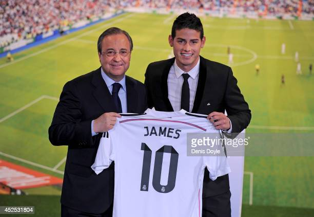 James Rodriguez holds his new Real shirt beside club president Florentino Perez during his unveiling as a new Real Madrid player at the Santaigo...