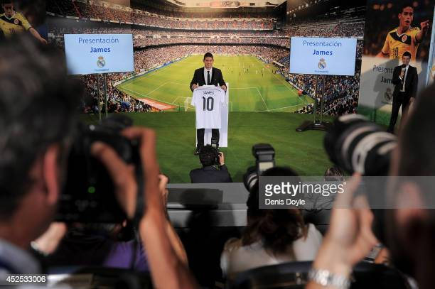 James Rodriguez holds his new Real shirt during his unveiling as a new Real Madrid player at the Santaigo Bernabeu stadium on July 22 2014 in Madrid...