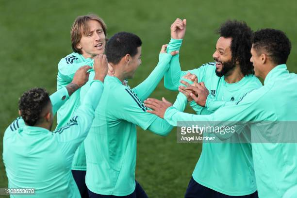 James Rodriguez Marcelo and Luka Modric share a joke during a training session ahead of their UEFA Champions League round of 16 first leg match...