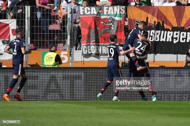 James Rodriguez of Bayern Muenchen celebrates with his team after he scored a goal to m are it 12 during the Bundesliga match between FC Augsburg and...
