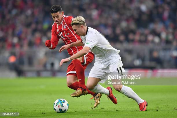 James Rodriguez of Bayern Muenchen fights for the ball with Felix Klaus of Hannover during the Bundesliga match between FC Bayern Muenchen and...