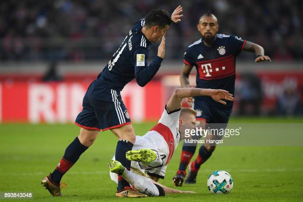 James Rodriguez of Bayern Muenchen fights for the ball with Timo Baumgartl of Stuttgart while Arturo Vidal of Bayern Muenchen looks on during the...