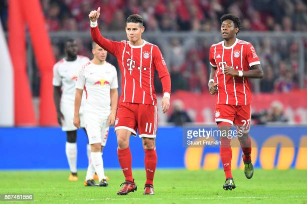 James Rodriguez of Bayern Muenchen gives a thumbs up after he scored his teams first goal to make it 10 as David Alaba of Bayern Muenchen looks on...