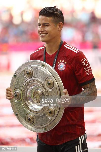 James Rodriguez of Bayern Muenchen poses with the champions trophy after the Bundesliga match between FC Bayern Muenchen and VfB Stuttgart at Allianz...