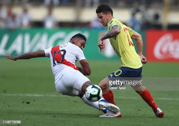 James Rodriguez of Colombia and Renato Tapia of Peru compete for the ball during a friendly match between Peru and Colombia at Estadio Monumental on...