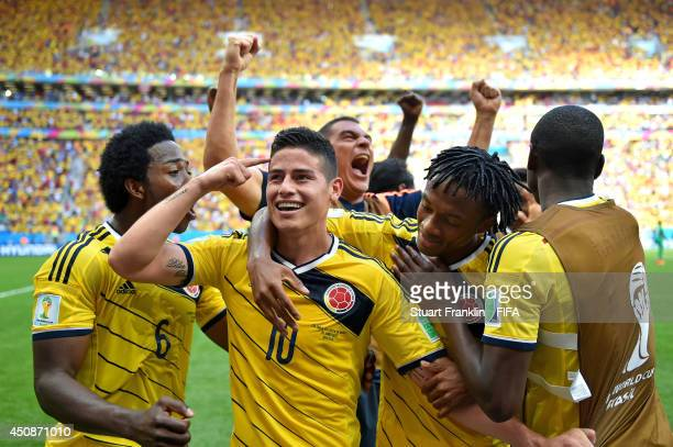 James Rodriguez of Colombia celebrates scoring his team's first goal with his teammates during the 2014 FIFA World Cup Brazil Group C match between...