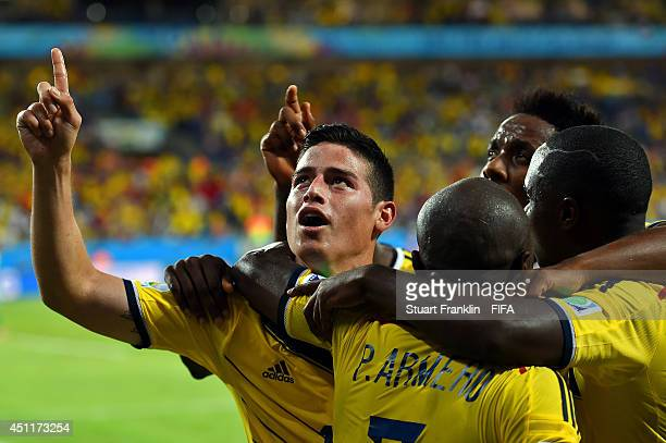 James Rodriguez of Colombia celebrates scoring his team's fourth goal with his teammates during the 2014 FIFA World Cup Brazil Group C match between...
