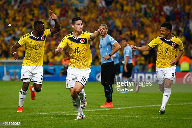 James Rodriguez of Colombia celebrates scoring his team's second goal and his second of the game with teammates Jackson Martinez and Teofilo...