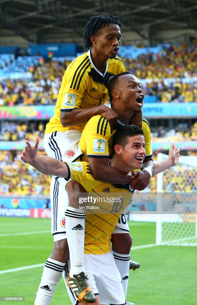 James Rodriguez of Colombia (bottom) celebrates scoring his team's third goal with Juan Guillermo Cuadrado (top) and Juan Camilo Zuniga (middle) during the 2014 FIFA World Cup Brazil Group C match between Colombia and Greece at Estadio Mineirao on June 14, 2014 in Belo Horizonte, Brazil.