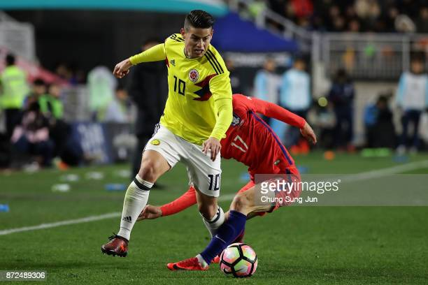 James Rodriguez of Colombia compete for the ball with Lee JaeSung of South Korea during the international friendly match between South Korea and...