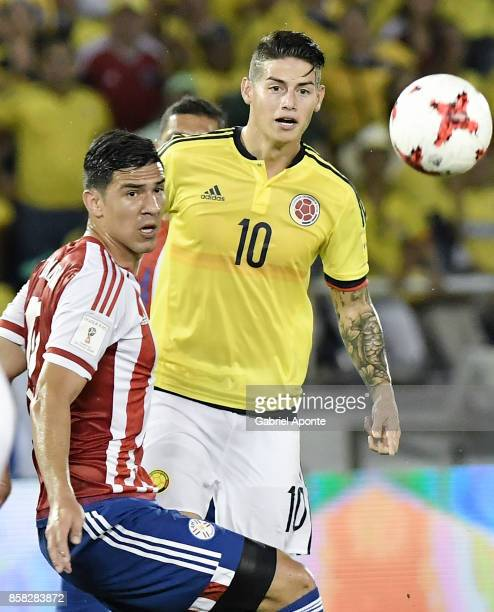 James Rodriguez of Colombia looks at the ball with Fabian Balbuena of Paraguay during a match between Colombia and Paraguay as part of FIFA 2018...