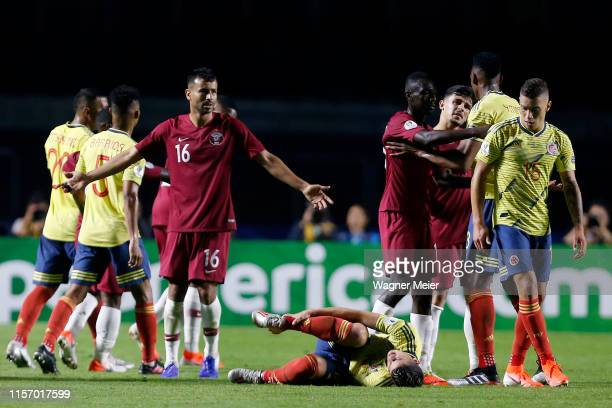 James Rodriguez of Colombia on the ground reacts after an injury as Boualem Khoukhi of Qatar reacts during the Copa America Brazil 2019 group B match...