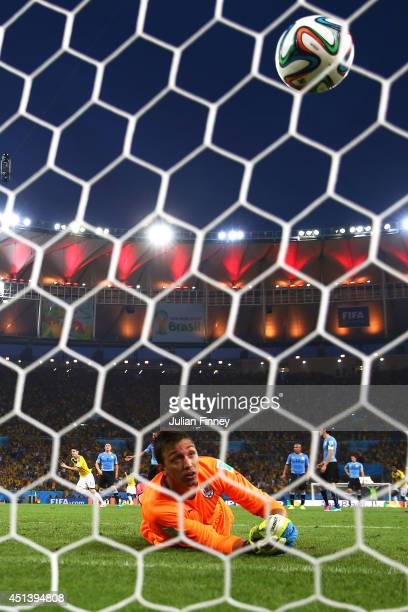 James Rodriguez of Colombia scores his team's first goal past Fernando Muslera of Uruguay during the 2014 FIFA World Cup Brazil round of 16 match...