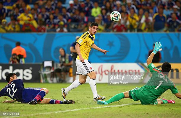 James Rodriguez of Colombia shoots and scores his team's fourth goal past goalkeeper Eiji Kawashima of Japan during the 2014 FIFA World Cup Brazil...