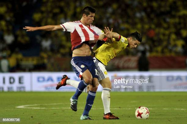 James Rodriguez of Colombia vies for the ball with Fabian Balbuena of Paraguay during a match between Colombia and Paraguay as part of FIFA 2018...