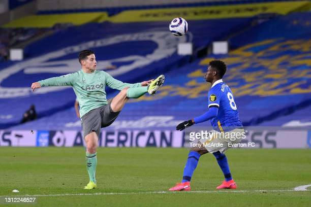 James Rodriguez of Everton and Yves Bissouma challenge for the ball during the Premier League match between Brighton and Hove Albion and Everton at...