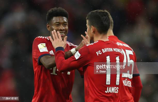 James Rodriguez of FC Bayern Muenchen celebrates his first goal with teammate David Alaba during the Bundesliga match between FC Bayern Muenchen and...