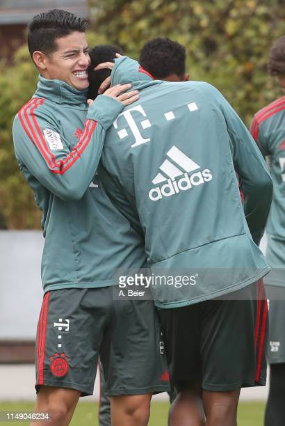 James Rodriguez of FC Bayern Muenchen jokes with his teammate Alphonso Davies before a training session at the club's Saebener Strasse training...