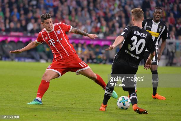 James Rodriguez of Muenchen and Nico Elvedi of Moenchengladbach battle for the ball during the Bundesliga match between FC Bayern Muenchen and...