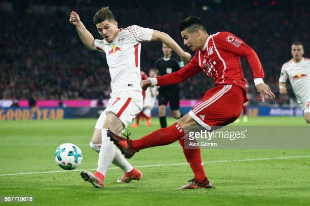 James Rodriguez of Muenchen is challenged by Marcel Sabitzer of Leipzig during the Bundesliga match between FC Bayern Muenchen and RB Leipzig at...