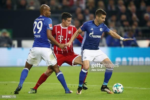 James Rodriguez of Muenchen is challenged by Naldo and Matija Nastasic of Schalke during the Bundesliga match between FC Schalke 04 and FC Bayern...