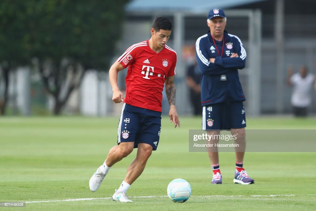 James Rodriguez of Muenchen runs with the ball next to his head coach Carlo Ancelotti during a training session at Geylang Field during the Audi Summer Tour 2017 on July 24, 2017 in Singapore.