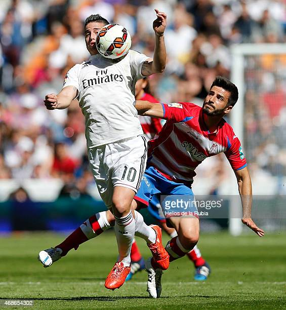 James Rodriguez of Real Madrid and Fran Rico of Granada cf compete for the ball during the La Liga match between Real Madrid CF and Granda CF at...