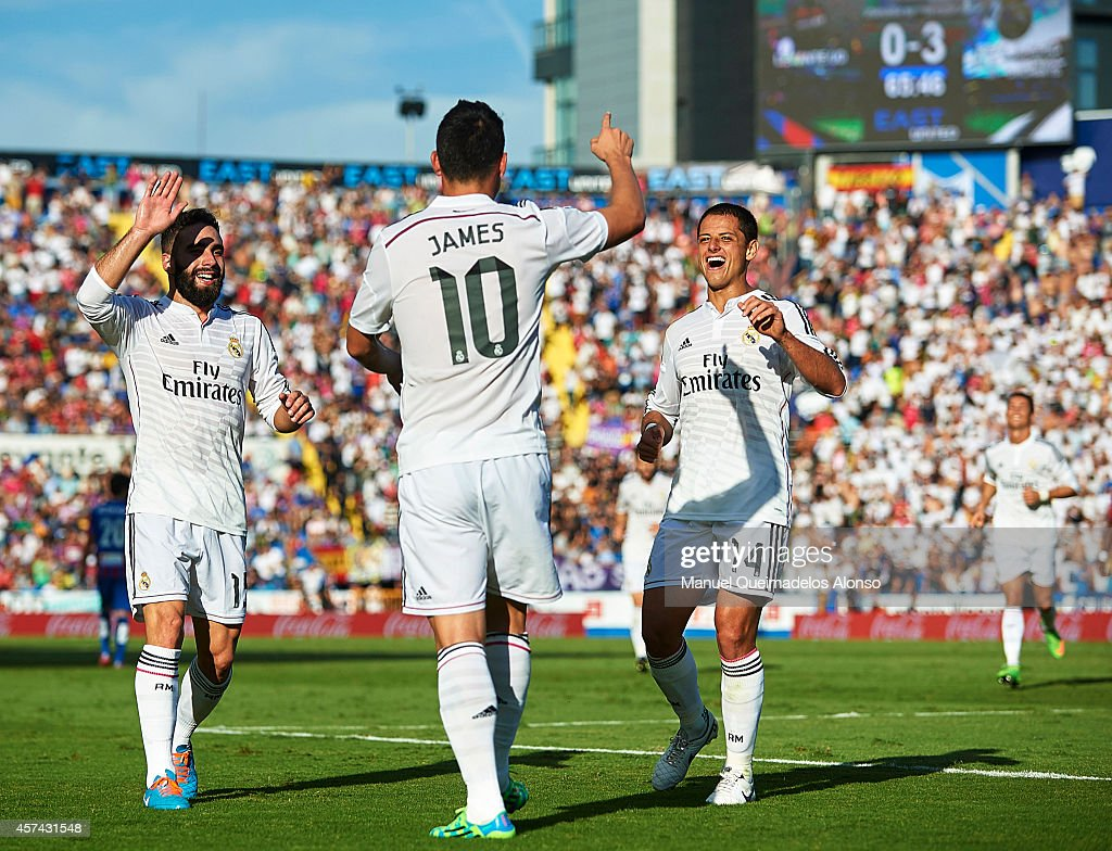 James Rodriguez of Real Madrid celebrates after scoring with his teammates Daniel Carvajal (L) and Javier 'Chicharito' Hernandez (R) during the La Liga match between Levante UD and Real Madrid at Ciutat de Valencia on October 18, 2014 in Valencia, Spain.