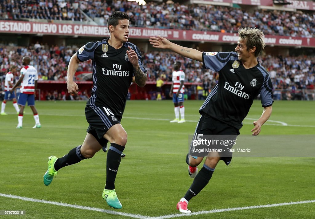 James Rodriguez (L) of Real Madrid celebrates with Fabio Coentrao after scoring their team's second goal during the La Liga match between Granada CF and Real Madrid CF at Estadio Nuevo Los Carmenes on May 6, 2017 in Granada, Spain.