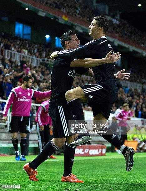 James Rodriguez of Real Madrid CF celebrates scoring their second goal with teammate Cristiano Ronaldo during the La Liga match between Rayo...