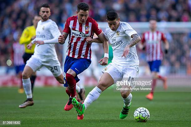 James Rodriguez of Real Madrid CF competes for the ball with Jose Maria Gimenez of Atletico de Madrid during the La Liga match between Real Madrid CF...