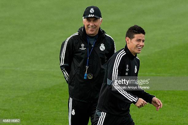 James Rodriguez of Real Madrid CF laughs ahead his head coach Carlo Ancelotti during the training session ahead of the UEFA Champions League Group B...