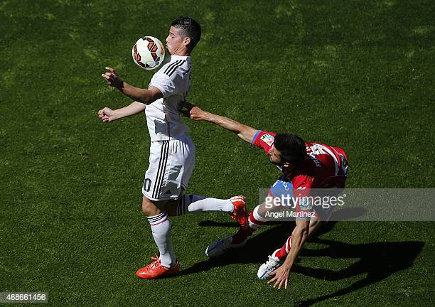 James Rodriguez of Real Madrid controls the ball under pressure from Fran Rico of Granada CF during the La Liga match between Real Madrid CF and...