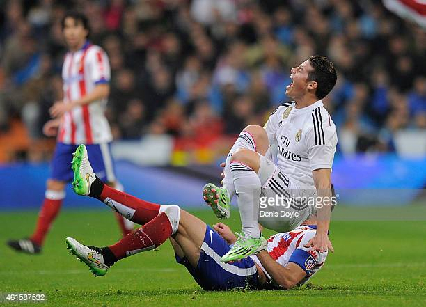 James Rodriguez of Real Madrid is tackled by Raul Garcia of Atletico de Madrid during the Copa del Rey Round of 16 Second leg match between Real...
