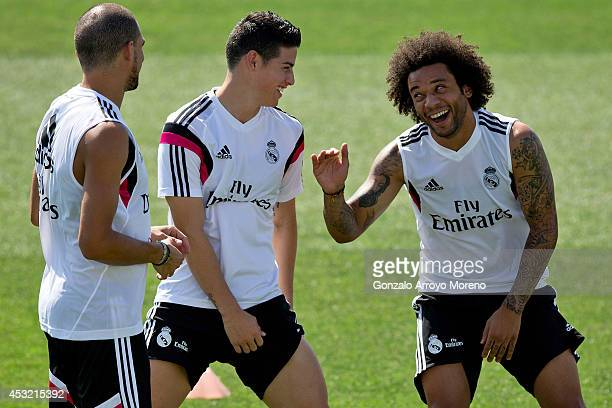 James Rodriguez of Real Madrid joks with teammates Marcelo and Karim Benzema during a Real Madrid training session at Valdebebas training ground on...