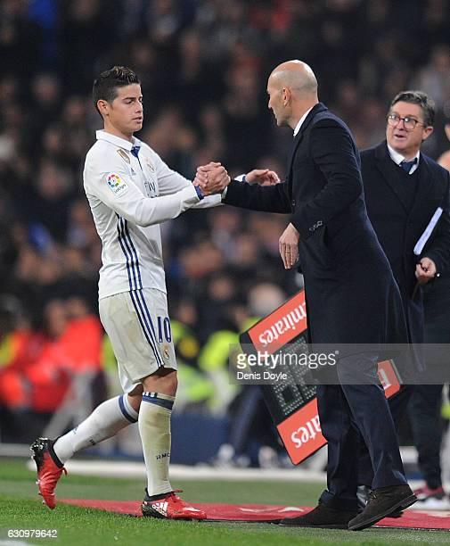James Rodriguez of Real Madrid shakes hands with his manager Zinedine Zidane after being substituted during the Copa del Rey Round of 16 First Leg...