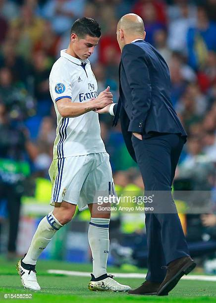 James Rodriguez of Real Madrid shakes hands with Zinedine Zidane Manager of Real Madrid as he is replaced during the UEFA Champions League Group F...