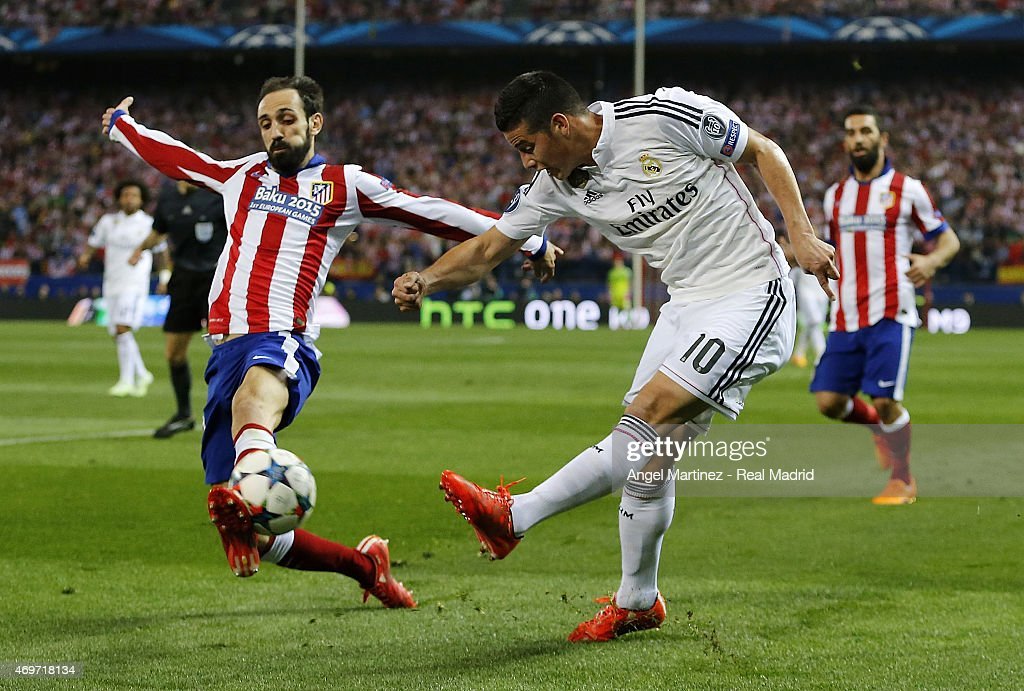 James Rodriguez of Real Madrid shoots on goal under pressure from Juanfran Torres of Atletico de Madrid during the UEFA Champions League Quarter Final first leg match between Club Atletico de Madrid and Real Madrid CF at Vicente Calderon Stadium on April 14, 2015 in Madrid, Spain.