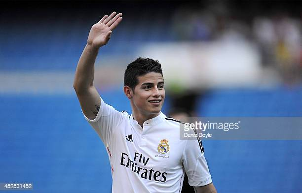 James Rodriguez waves to fans during his unveiling as a new Real Madrid player at the Santaigo Bernabeu stadium on July 22 2014 in Madrid Spain Real...