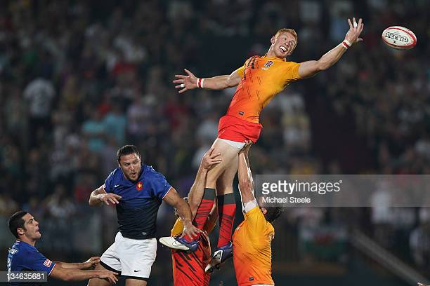James Rodwell of England flicks the ball on at a line out during the Final match between England and France on Day Three of the IRB Dubai Sevens at...