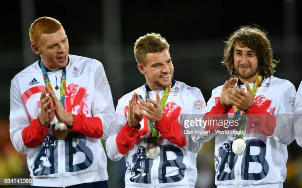 James Rodwell Tom Mitchell and Dan Bibby of Great Britain applaud on the podium after receiving their silver medals following the Men's Rugby Sevens...