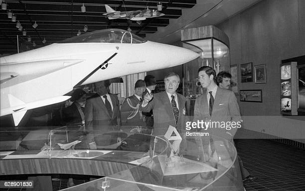 James S McDonnell founder and board chairman of McDonnell Douglas Corporation discusses with Prince Charles a model of the McDonnell produced F15...