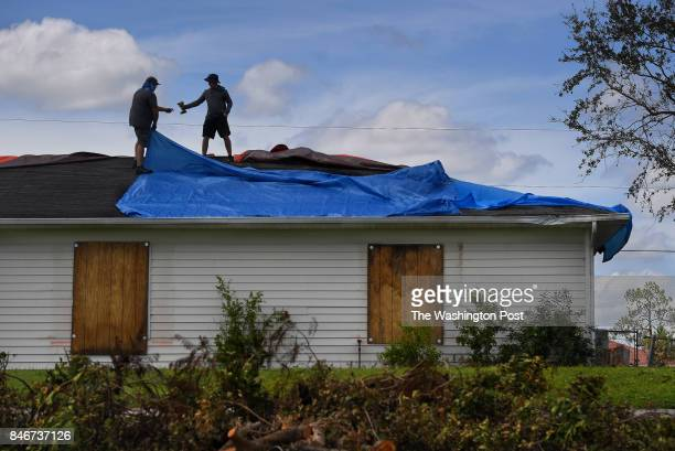 James Saunders gets a drill handed to him by his 15yearold son Parker Saunders as they worked to cover the damaged roof of the family home in Lehigh...