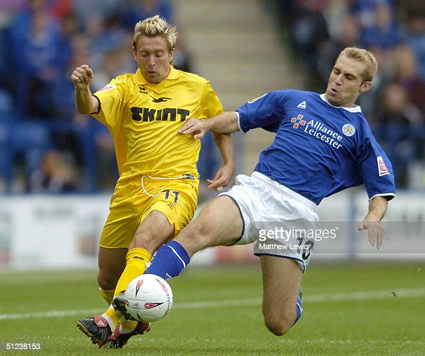 James Scowcrofyt of Leicester tackles Darren Currie of Brighton during the CocaCola Championship match between Leicester City and Brighton and Hove...