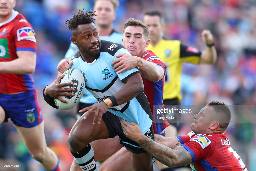 James Segeyaro of the Sharks is tackled by Connor Watson and Shaun Kenny-Dowall of the Knights during the round 12 NRL match between the Newcastle Knights and the Cronulla Sharks at McDonald Jones Stadium on May 27, 2018 in Newcastle, Australia.