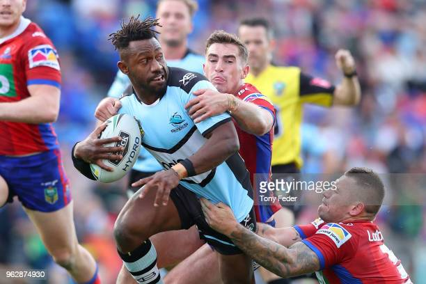 James Segeyaro of the Sharks is tackled by Connor Watson and Shaun KennyDowall of the Knights during the round 12 NRL match between the Newcastle...