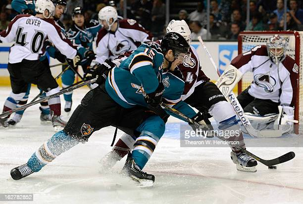 James Sheppard of the San Jose Sharks gets an assist passing the puck by Greg Zanon of the Colorado Avalanche to teammate TJ Galiardi who scored on...